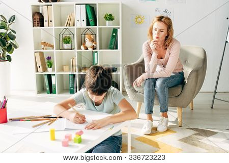 Kid With Dyslexia Painting With Pencil And Child Psychologist Looking At Him