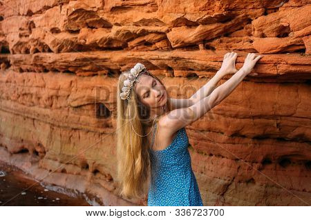 Young Woman With Closed Eyes And Threw Back Head In Crown From Shells Staying Near Red Sand Wall Nea