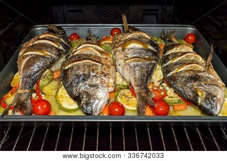 Roasted Dorada Fish With Vegetables And Lemon In The Oven. Healthy Food. Fitness Dinner.
