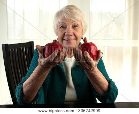 Attractive Gray-haired Elderly Woman Holds Pomegranates In Her Hands. Pomegranates Fruits Are Symbol