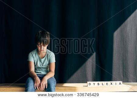 Sad Kid With Dyslexia Sitting Near Wooden Cubes With Lettering Dyslexia On Black Background