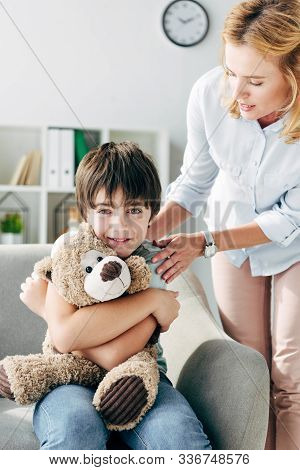 Smiling Kid With Dyslexia Holding Teddy Bear And Child Psychologist Looking At Him