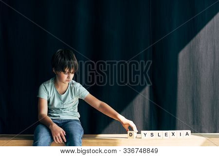 Kid With Dyslexia Playing With Wooden Cubes With Lettering