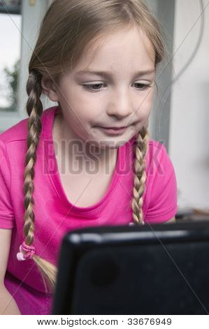 little girl learning at laptop