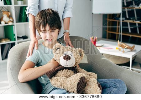 Cropped View Of Child Psychologist Hugging Kid With Dyslexia Holding Teddy Bear