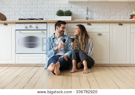 Happy Affectionate Couple Talking Drinking Wine Sit On Kitchen Floor