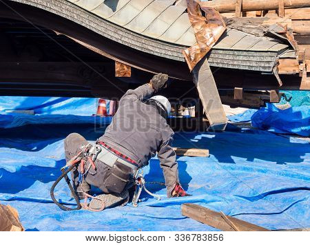 Aso, Japan - November 5, 2016: Roof Of Collapsed Hall Being Carefully Lifted By Workers In Heavily D