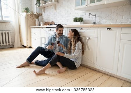 Romantic Couple Sit On Warm Kitchen Floor Talking Drinking Wine