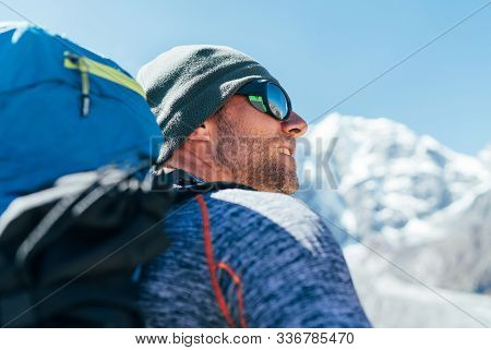 Portrait Of Unshaved Hiker Man With Backpack And Uv Protecting Sunglasses On Taboche 6495m Peakk Bac