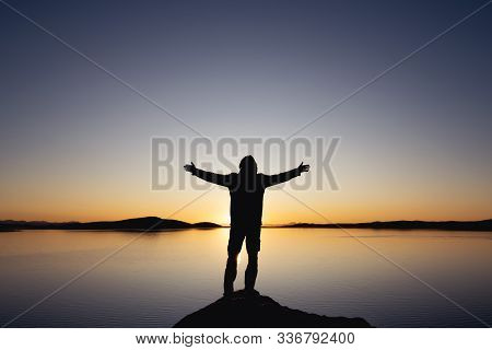 Mans Silhouette Stands With Raised Arms Against Sunset Lake And Mountains