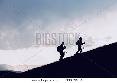 Two Hikers Silhouettes Goes Together Uphill In Mountains Against Clouds