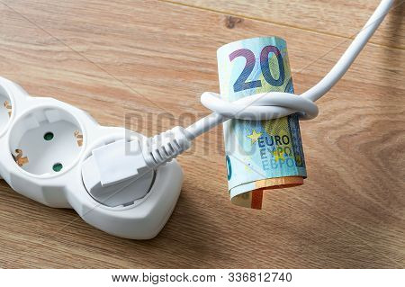 White Electric Cable With Plug Tied To A Knot On A Roll Of Euro Banknotes. Cost Of Electricity And E