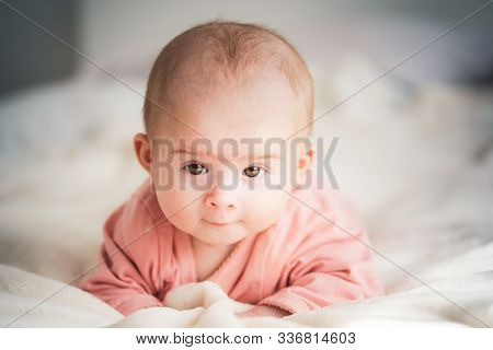 Cute Baby Girl On Bed Looking At Camera With Smug Look.