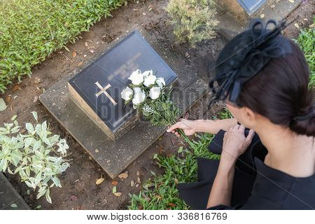 Mourning Young Woman Laying White Flowers On Her Family Grave In Beautiful Green Cemetery.