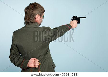 Man in the uniform of a military officer fires a gun.