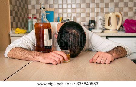 Alcoholic Drink And Drunken Man In Kitchen