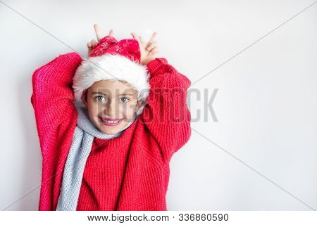 7 Yaers Old Smiling Girl With Changing Tees Smiling In Santa Hat, Red Pullover, Gray Scarf, Imitatio