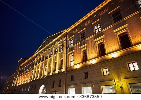 The facade of a historic tenement house in the neoclassical style at night in Poznan poster