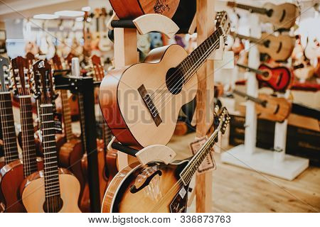 Many Colorful Wooden Guitars Put On Guitar Stand In Store Showroom. Background Guitar Shop And Music