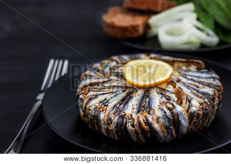 Pilaf With Hamsi Anchovy Fish. Traditional Turkish Food - Kapama Pilav - On Black Wooden Table.