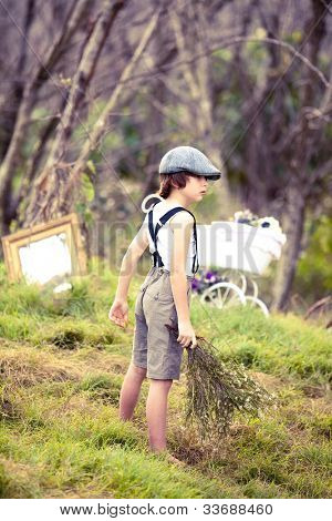 Young boy in retro clothing in woodland