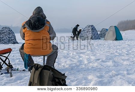 Winter Fishing. Man, Fisherman, In Warm Winter Clothes Sitting On The Ice Of The River, Lake, Fishin