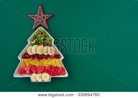 Christmas Background With Fruit Salad In Fir Tree Shaped Plate And Copy Space For Text. Top View Fla