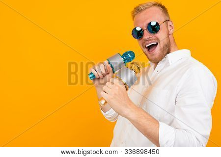 Cheeky European Man In A White Shirt Sings Into Two Microphones On A Yellow Background