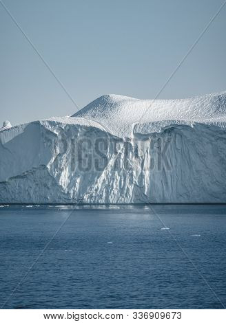 Greenland. The Biggest Glacier On A Planet Jakobshavn. Huge Icebergs Of Different Forms In The Gulf.