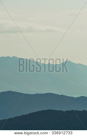 Hills In Blue Haze On Horizon. Silhouettes Of Mountains In Valley At Sunset