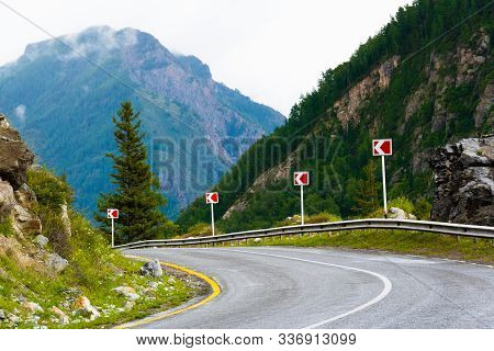 Asphalt Road In Mountain Valley With Ridge Of Rocks On Horizon. Comfortable Travel By Car In Wild