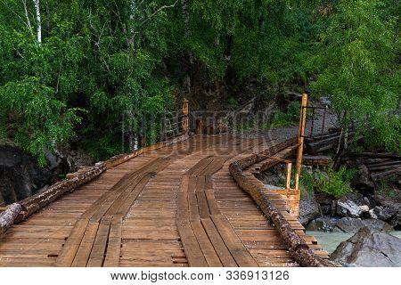 Wooden Bridge Of Boards Across Mountain River. Rural Old Bridge In Forest