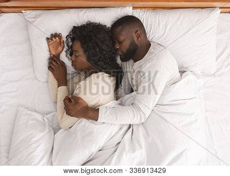Black Married Couple Sleeping In Bed And Cuddling, Husband Tenderly Hugging Wife From Back, Top View