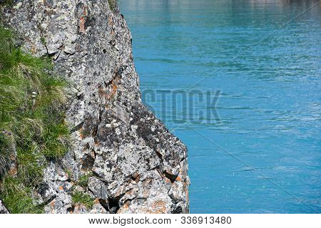 Rock On Shore Of Blue Sea. Turquoise Mountain Lake, The Surface Of River