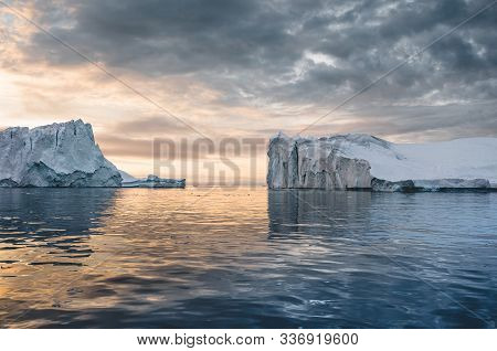 Bright Sunny Day In Antarctica. Full Calm And Reflection Of Icebergs In Deep Clear Water. Travel By