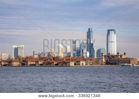 New York, Usa - November 25 2019: The Old Immigration Station At Ellis Island With Jersey City In Th