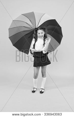 Its More Than Ok. Happy Small Schoolchild Gesturing Ok On Yellow Background. Little Girl Smiling Wit
