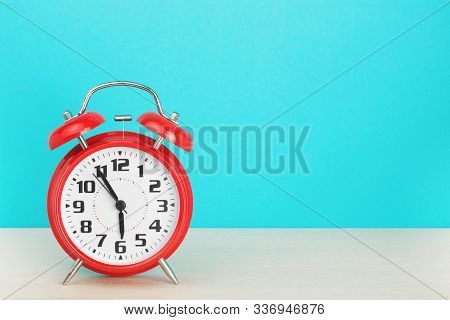 Red Retro Alarm Clock With Five Minutes To Six Oclock, On Wooden Table On A Blue Background. The Con