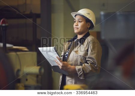 Waist Up Portrait Of Female Foreman Holding Clipboard While Supervising Production At Factory, Copy