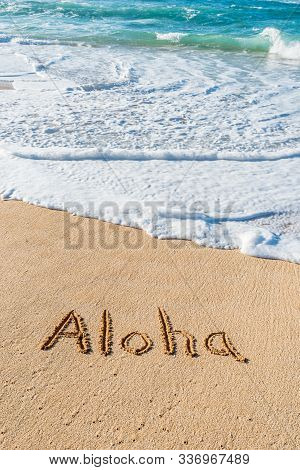 The Word Aloha Written In The Sand On The Beach With A Wave Washing In