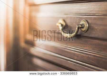 Selective Focus Of Brass Handle On Antique Cabinet With Warm Light