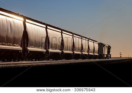Train Of Covered Hoppers Glinting In Sunrise