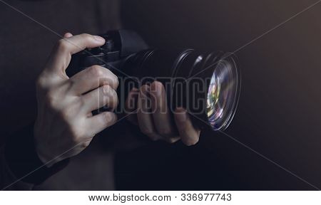 Young Photographer Woman Using Camera To Taking Photo. Dark Tone. Selective Focus On Hand