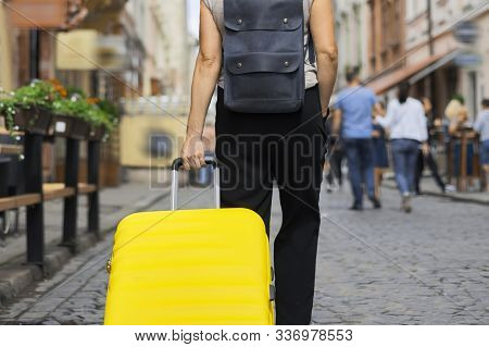 Luggage Travel Tourism Concept, Closeup Of Yellow Suitcase In Hand Of Walking Woman In Tourist City,