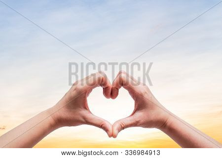 Woman Hold Hands Up To Sky In The Shape Of Love Heart On Nature Sun Light Flare And Cloud With Sky B