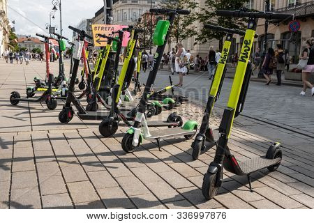 Warsaw, Poland - July 21, 2019: Many electric scooters, escooter or e-scooter of the ride sharing company Hive left on sidewalk in Warsaw, Poland