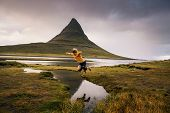 Young hiker jumps over a stream at the Kirkjufell mountain in Iceland. This 463 m high mountain is located on the north coast of Icelands Snaefellsnes peninsula. poster