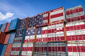 The National Flag Of Usa On A Large Number Of Metal Containers For Storing Goods Stacked In Rows On