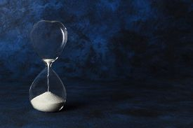 Time Is Running Out Concept. An Hourglass With Sand Falling Through, On A Dark Blue Background With