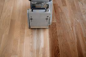 Scraping Hardwood Floor With The Grinding Machine. Repair In The Apartment. Carpenter Doing Parquet